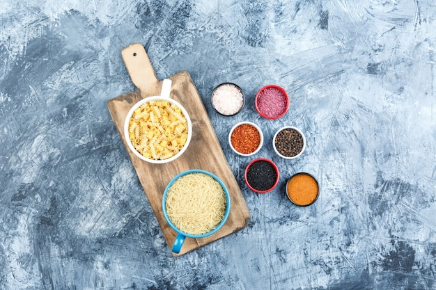 Alcuni assortiti di pasta con spezie in ciotole su intonaco grigio e sfondo tagliere, vista dall'alto.