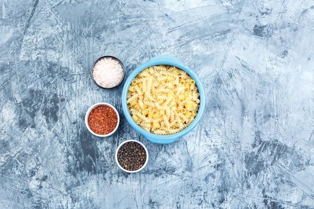 회색 석고 배경, 평면도에 그릇에 향신료와 일부 모듬 된 파스타.