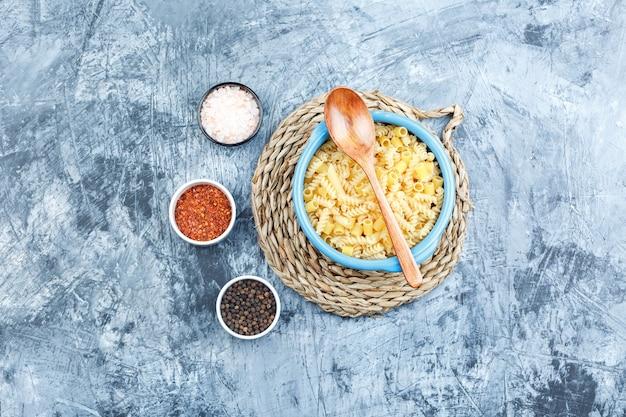 スパイス、灰色の漆喰と枝編み細工品のプレースマットの背景、上面図のボウルに木のスプーンといくつかの各種パスタ。