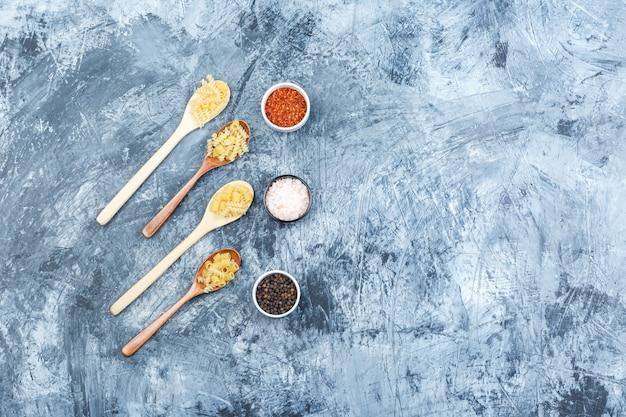 Alcuni assortiti di pasta con spezie in cucchiai di legno su una sgangherata sfondo intonaco, piatto laici.