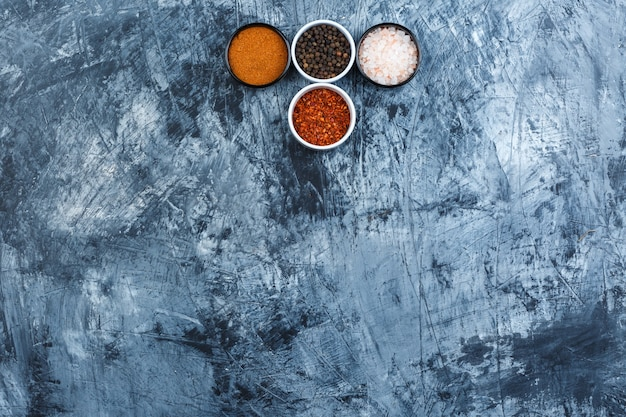 Some assorted spices in small bowls on grey plaster background, top view.