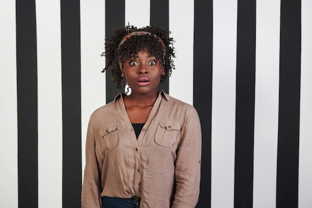 Some bad news. beautiful female portrait on the black and blue stripes type background. african american girl makes shocked face