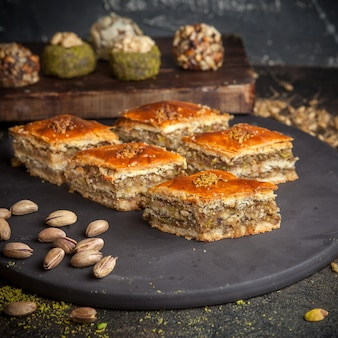 Some baklava with cookies on background on a black rounded platform side view.