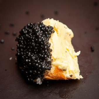 Some black caviar with butter on bread on dark background, high angle view.