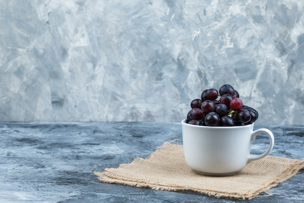 Some black grapes in a white cup on grunge and piece of sack background, side view.