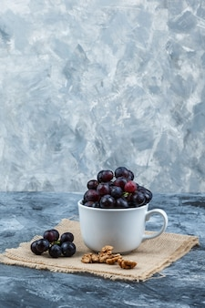 Some black grapes with walnuts in a white cup on grunge and piece of sack background, side view.