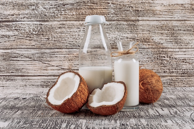 Some bottles of milk with divided in half coconut on white wooden background, side view.
