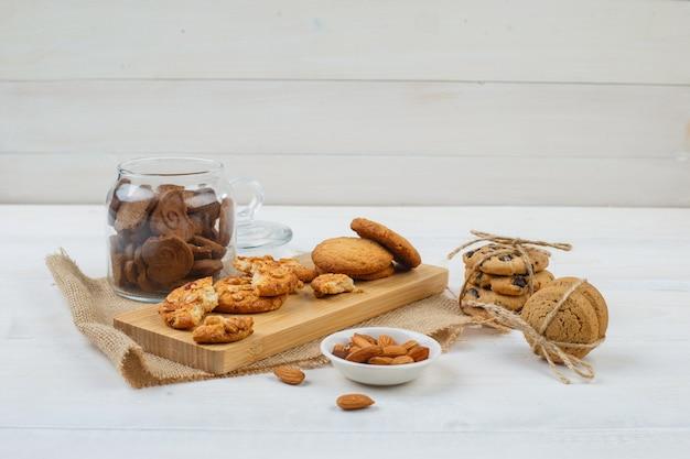 Alcuni biscotti marroni con mandorle in una ciotola, biscotti su un tagliere e un pezzo di sacco in un vasetto di vetro sulla superficie bianca