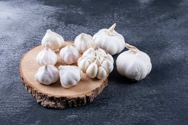 Some bunches of garlic on a wood stub and nearby on dark textured table