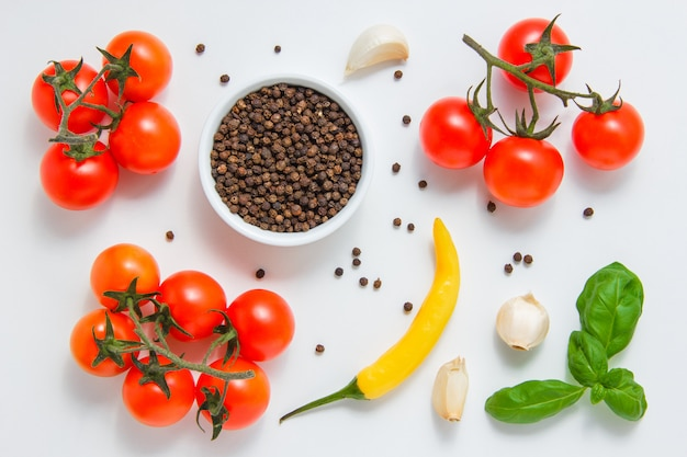 Some bunches of tomatoes with a bowl of black pepper, garlic, leaves, chili pepper on white surface top view.