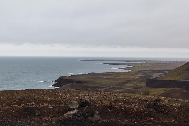アイスランドの曇りの日に海辺の道路を運転している車