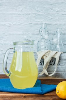 Some carafe of lemon juice with blue cloth, empty bottles on wooden and white surface, side view.