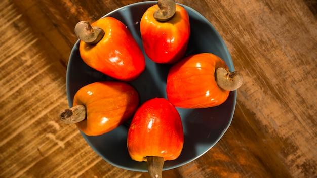 Некоторые фрукты кешью на деревянной поверхности.