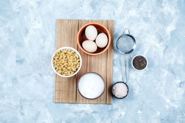 Alcuni cavatappi pasta con uova, yogurt, spezie, colino in una ciotola su sfondo grigio sgangherato e tagliere, vista dall'alto.