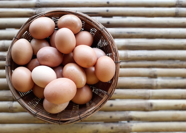 Some chicken eggs in the basket on the bamboo table