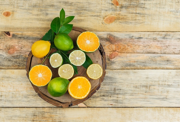 Some citrus fruits on a wooden board on wooden board