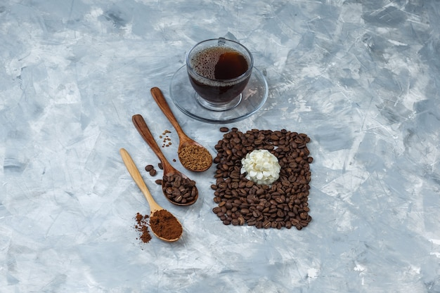 Some coffee beans, cup of coffee with coffee beans, instant coffee, coffee flour in wooden spoon