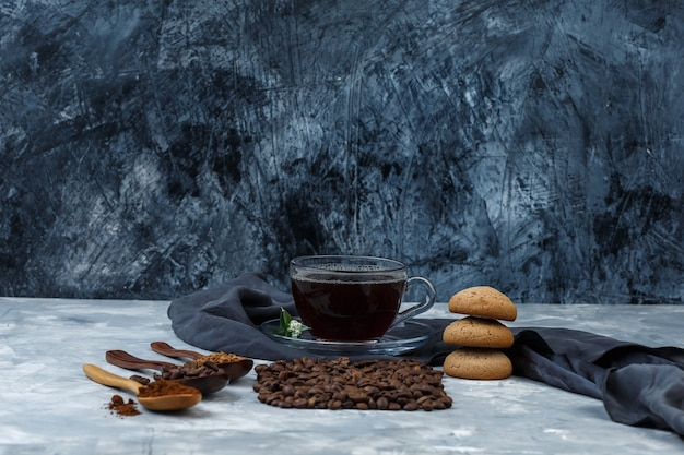 Some coffee beans, cup of coffee with coffee beans, instant coffee, coffee flour in wooden spoons