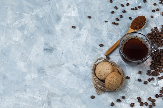 Some coffee beans, cup of coffee with coffee flour in wooden spoon, cookies, ropes on light blue marble background, flat lay.