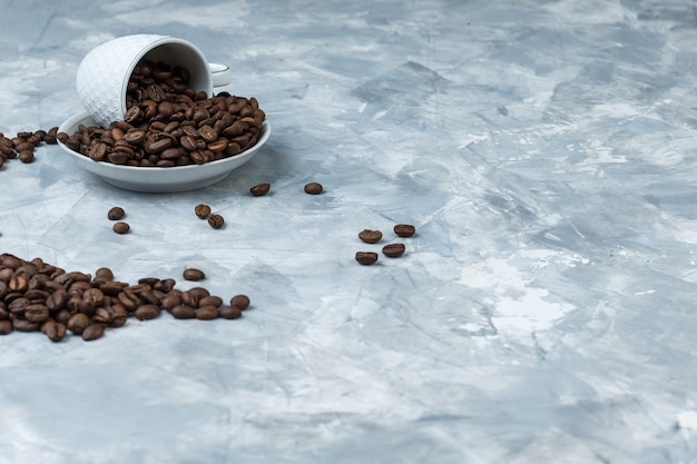 Some coffee beans in cup and plate on grey plaster background, high angle view.