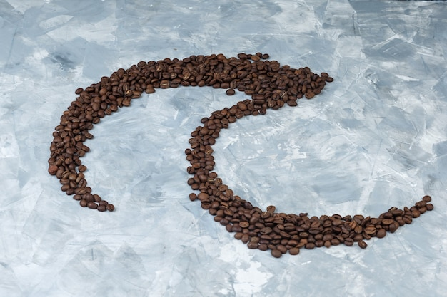 Some coffee beans on grey plaster background, high angle view.