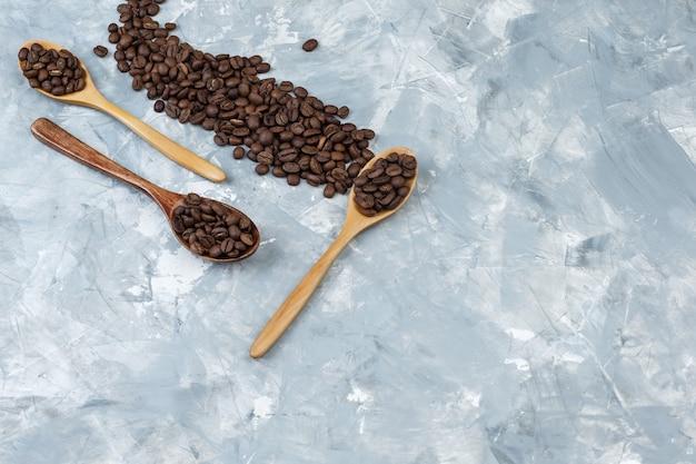 灰色の漆喰の背景に木のスプーンでいくつかのコーヒー豆、平らに横たわっていた。