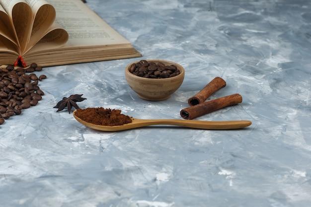Alcuni chicchi di caffè con libro, cannella, caffè istantaneo in cucchiaio di legno in una ciotola di legno su fondo di marmo azzurro, primo piano.