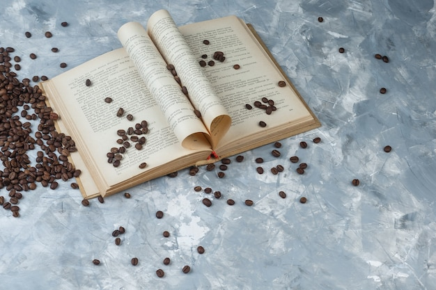 Some coffee beans with book on light blue marble background, high angle view.