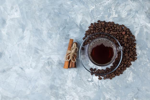 一杯のコーヒー、水色の大理石の背景にシナモン、フラットレイといくつかのコーヒー豆。あなたのテキストのための空きスペース