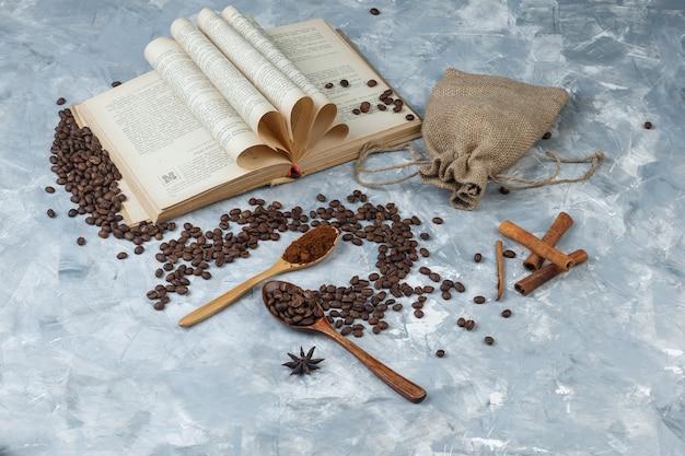 Alcuni chicchi di caffè con caffè macinato, libro, spezie, sacco in un cucchiaio di legno su una sgangherata sfondo grigio, ad alto angolo di visione.