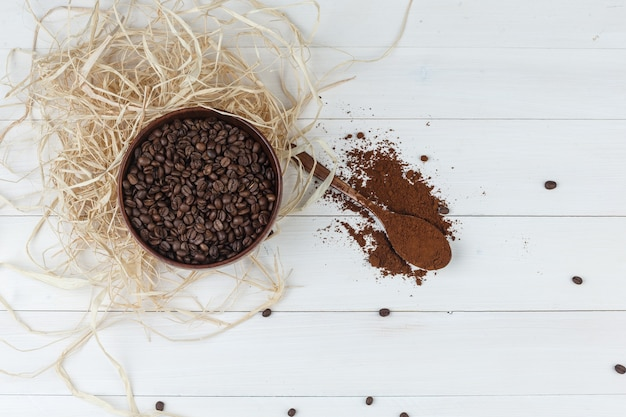 Some coffee beans with grinded coffee in a bowl on wooden background, top view.