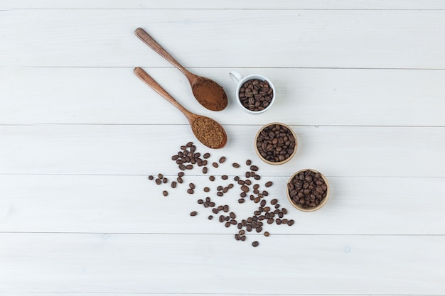 Some coffee beans with grinded coffee in cup and bowls on wooden background, top view.