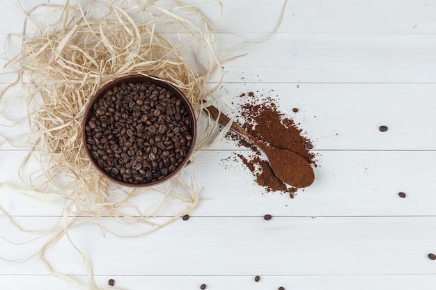 Некоторые кофейные зерна с молотым кофе в миске на деревянных фоне, вид сверху.