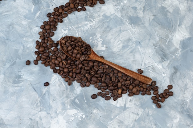 Some coffee beans in a wooden spoon on grey plaster background, flat lay.