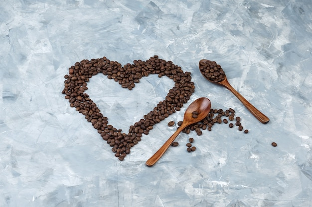 Some coffee beans in wooden spoons on grey plaster background, flat lay.