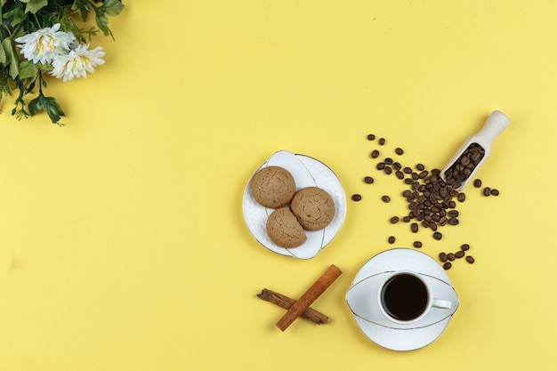 Some coffee with coffee beans, biscuits, cinnamon stick on yellow background