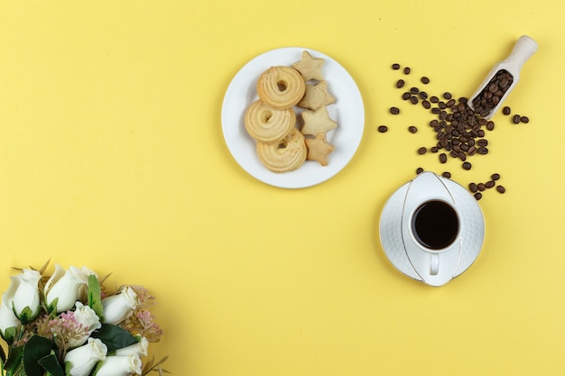 Some coffee with coffee beans and biscuits on yellow background