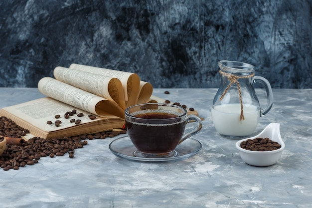 Some coffee with coffee beans, book, milk in a cup on grunge and plaster background, side view.