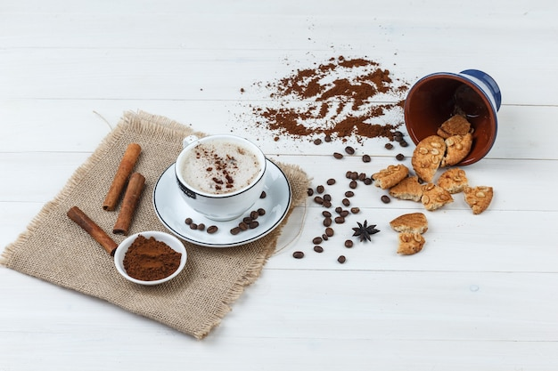 Some coffee with coffee beans, grinded coffee, cookies, cinnamon sticks in a cup on wooden and piece of sack background, high angle view.