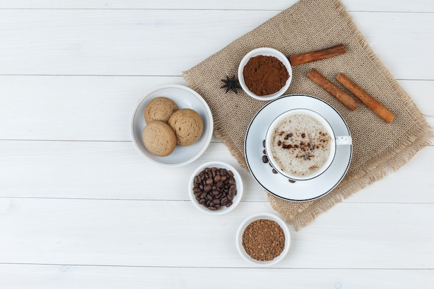 Some coffee with coffee beans, grinded coffee, spices, cookies in a cup on wooden and piece of sack background, top view.
