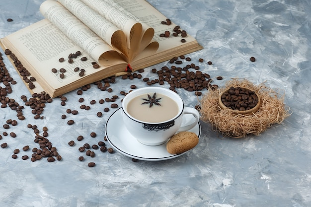Some coffee with cookies, coffee beans, book in a cup on grey plaster background, high angle view.