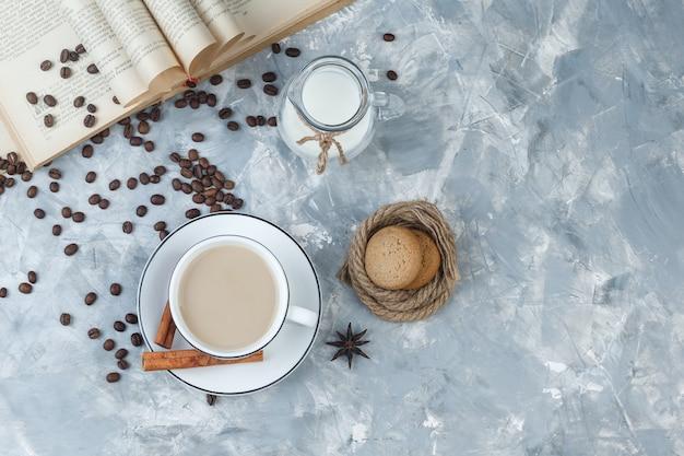 Немного кофе с печеньем, кофейными зернами, книгой, молоком, специями в чашке на сером гипсовом фоне, вид сверху.