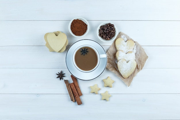 Some coffee with cookies, spices, coffee beans, grinded coffee in a cup on wooden background, top view.