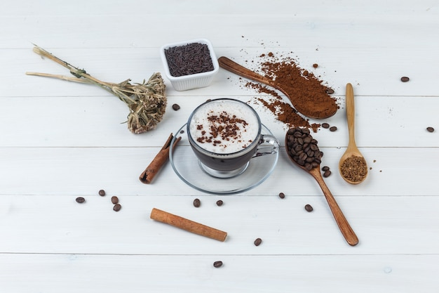 Some coffee with grinded coffee, coffee beans, cinnamon sticks, dried herbs in a cup