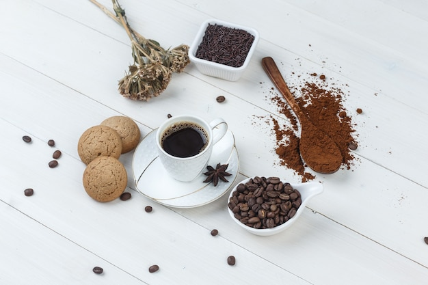 Some coffee with grinded coffee, coffee beans, dried herbs, cookies
