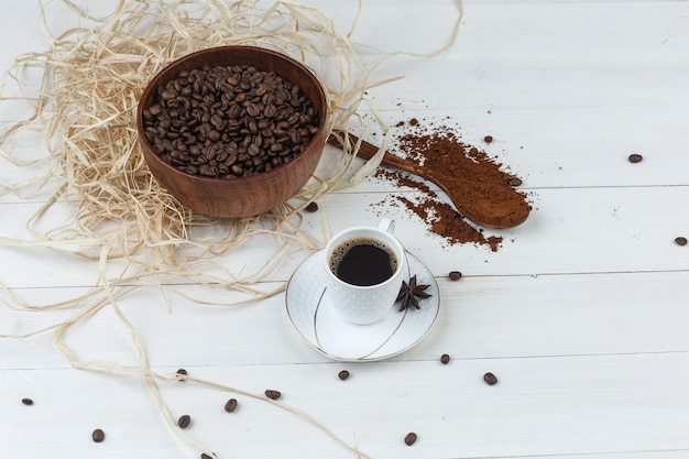 Un po 'di caffè con caffè macinato, chicchi di caffè, spezie in una tazza su sfondo di legno, ad alto angolo di visione.