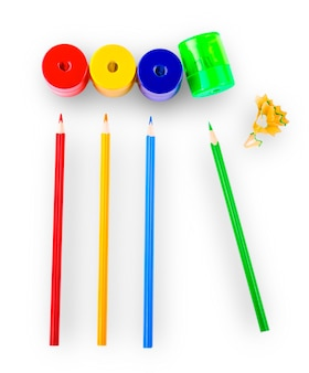 Несколько цветных карандашей разных цветов и точилки для карандашей и стружки для карандашей изолированы