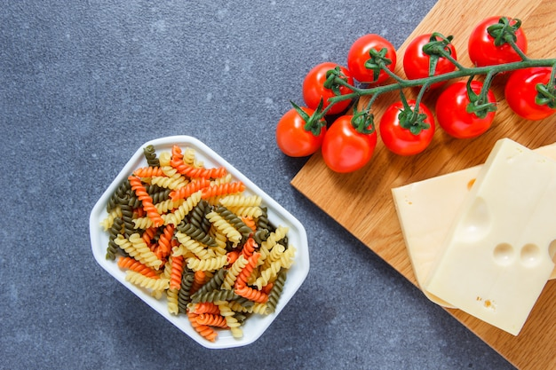 Some colorful macaroni pasta with tomatoes, cheese in a bowl on gray surface, top view.