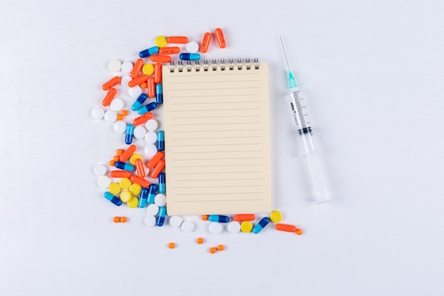 Some colorful pills with notepad and needle