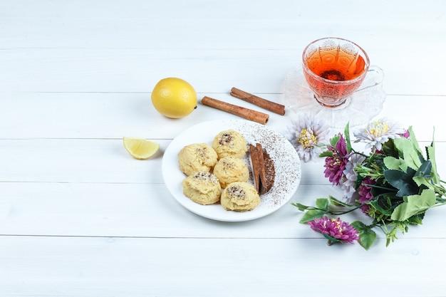 Некоторое печенье, чашка чая с корицей, лимоном, цветами на фоне белой деревянной доски, высокий угол обзора.